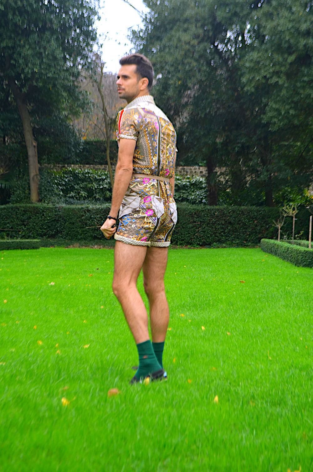 Caleb Garcia Taylor lounging in a garden in his bamboo silk jumper onesie design.