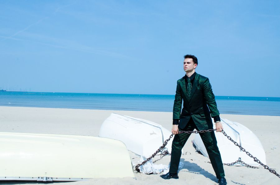 Eco-Couture Vegan Spy man on beach protecting planet in GSB Suit and Tie.