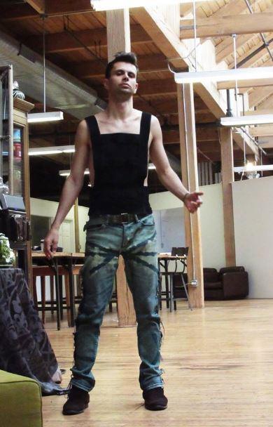 Cómodo Cal Garcia en sus favoritos Verdes Eco-Couture Jeans en el Diseñador de Estudio Loft. Aquí también vemos la alta costura camiseta sin mangas de forma ajustada con bloques semi-transparentes.