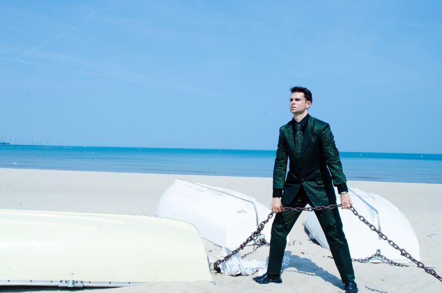 Eco-Couture vegan espía hombre en la playa protegeindo la planeta con GSB traje y corbata.